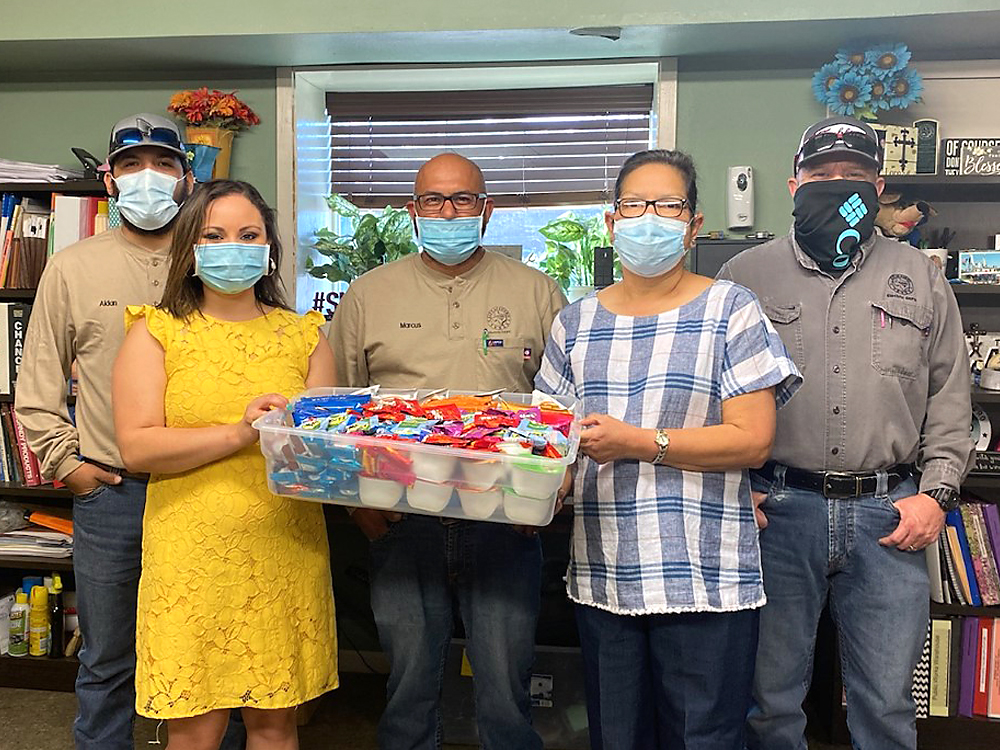 """Photo of December Events Committee presenting """"thank you"""" snack care package to City of Cuero Electrical Department"""