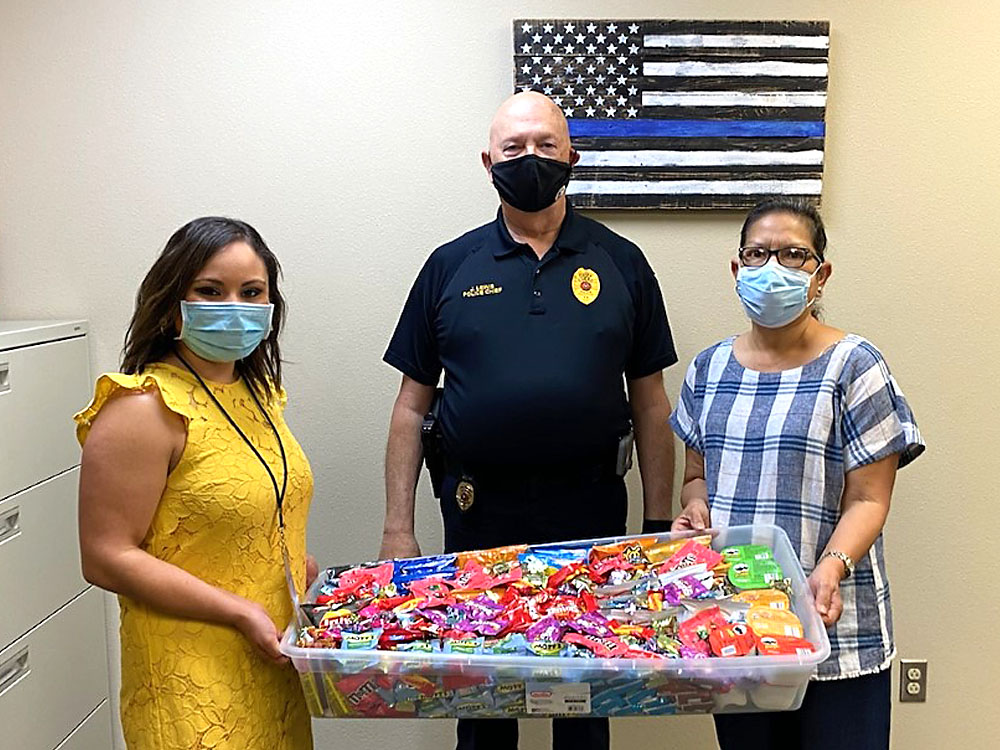 """Photo of December Events Committee presenting """"thank you"""" snack care package to City of Cuero Police Department"""