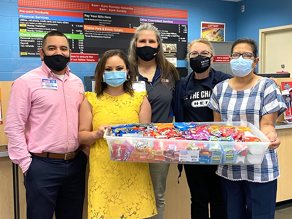 """Photo of December Events Committee presenting """"thank you"""" snack care package to H-E-B Grocery of Cuero"""