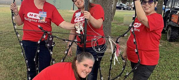H-E-B volunteers setting up deer display in scene in Cuero's Christmas in the Park