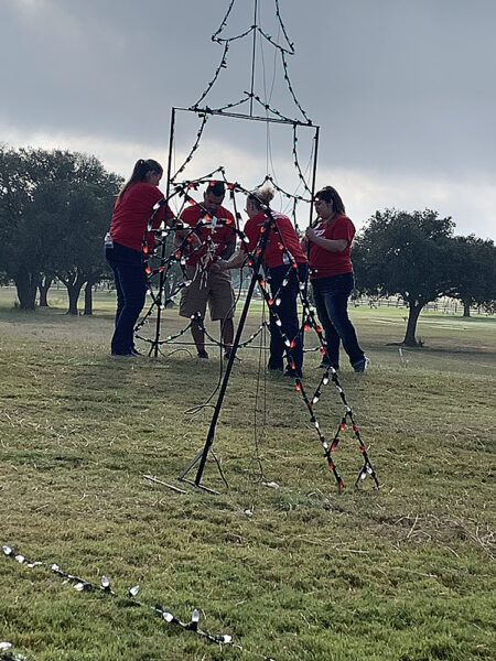 H-E-B volunteers setting up large tree display in scene for Cuero's Christmas in the Park