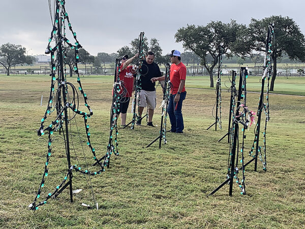 H-E-B volunteers setting up tree displays in scene for Cuero's Christmas in the Park