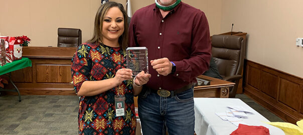 Samantha Bayfus (left) is presented with a plaque by Cuero City Manager Raymie Zella in recognition of her receipt of the City of Cuero 2020 Newton Rath Employee of the Year Award